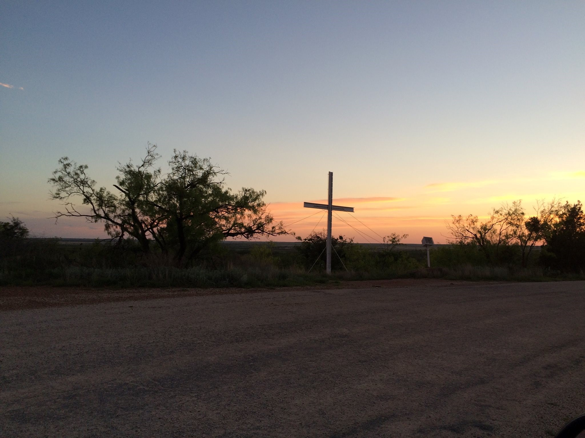 An open field with the sunset over by the mountains and a cross right on the middle of the photo.