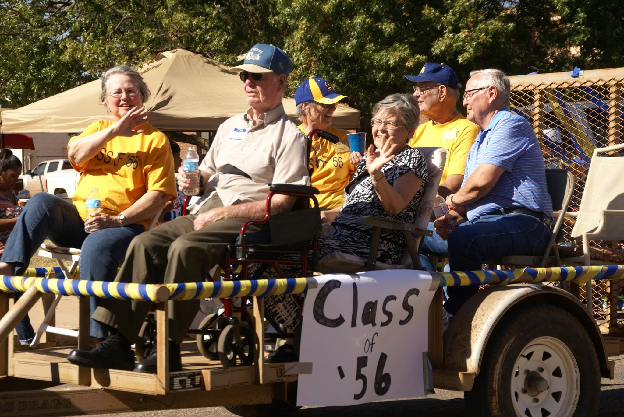 "A group of people all hopped on an allegory car with the poster of ""Class of '56"""