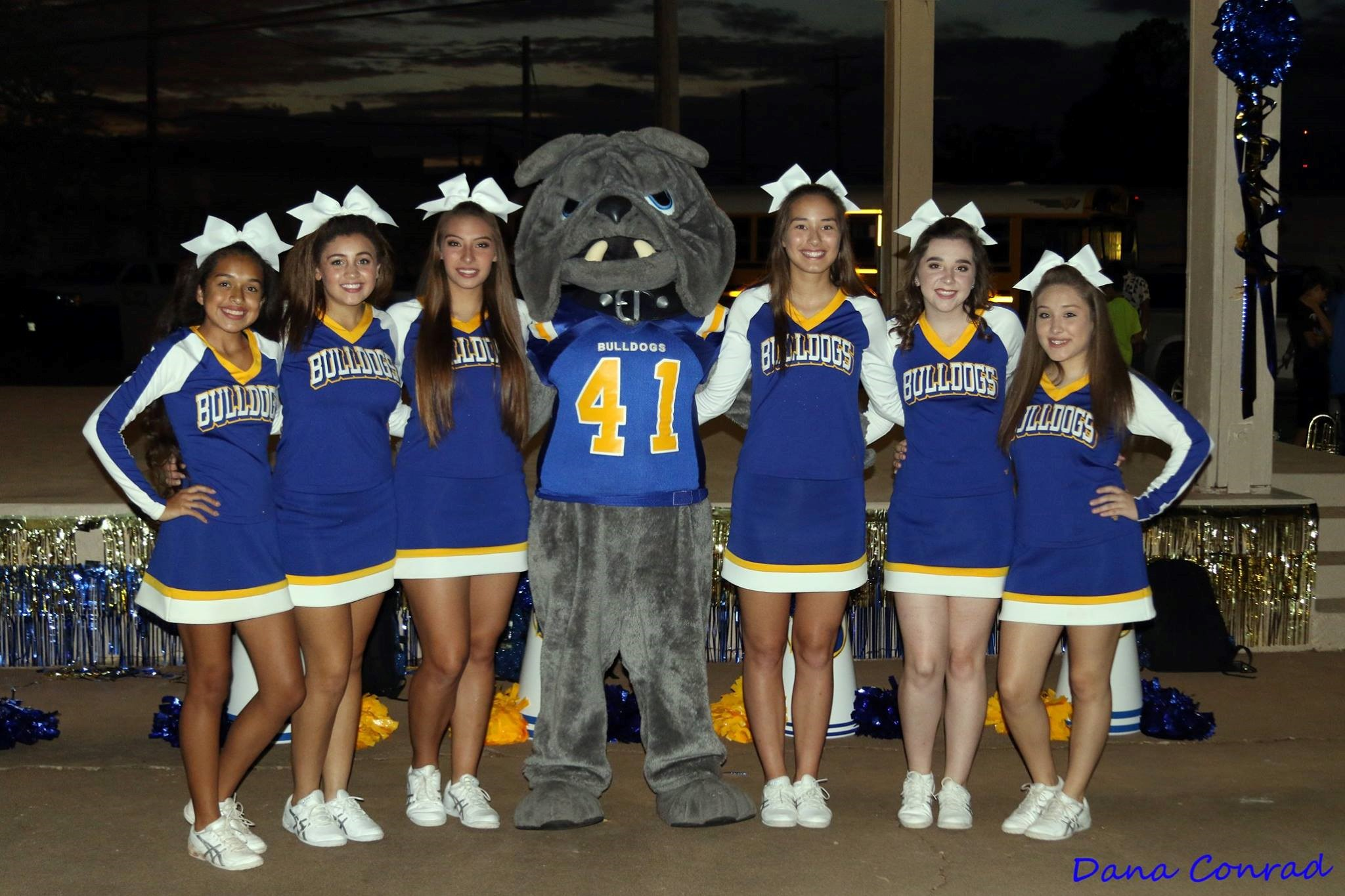 The cheerleaders all posing with the school's mascot.