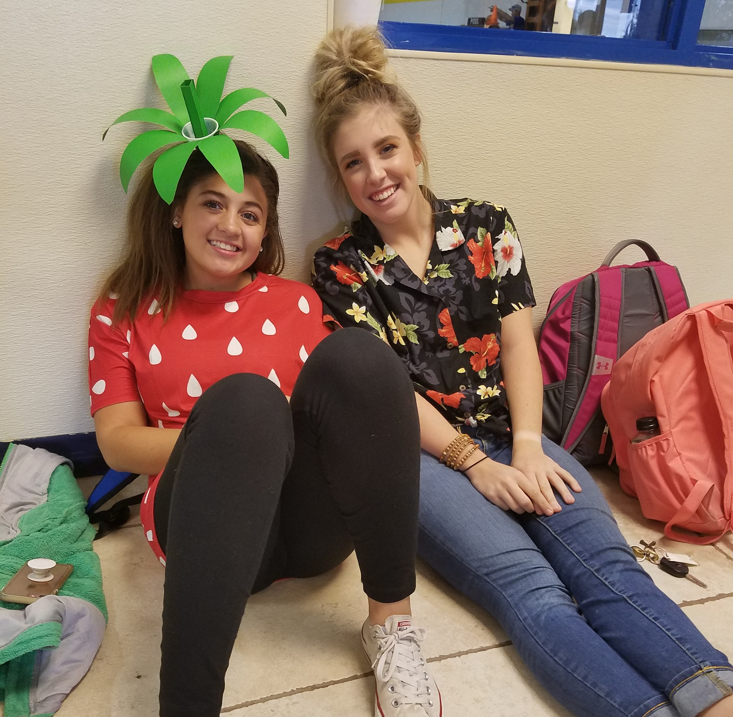 Two girls smiling at the picture, one of them dressed up as a strawberry.