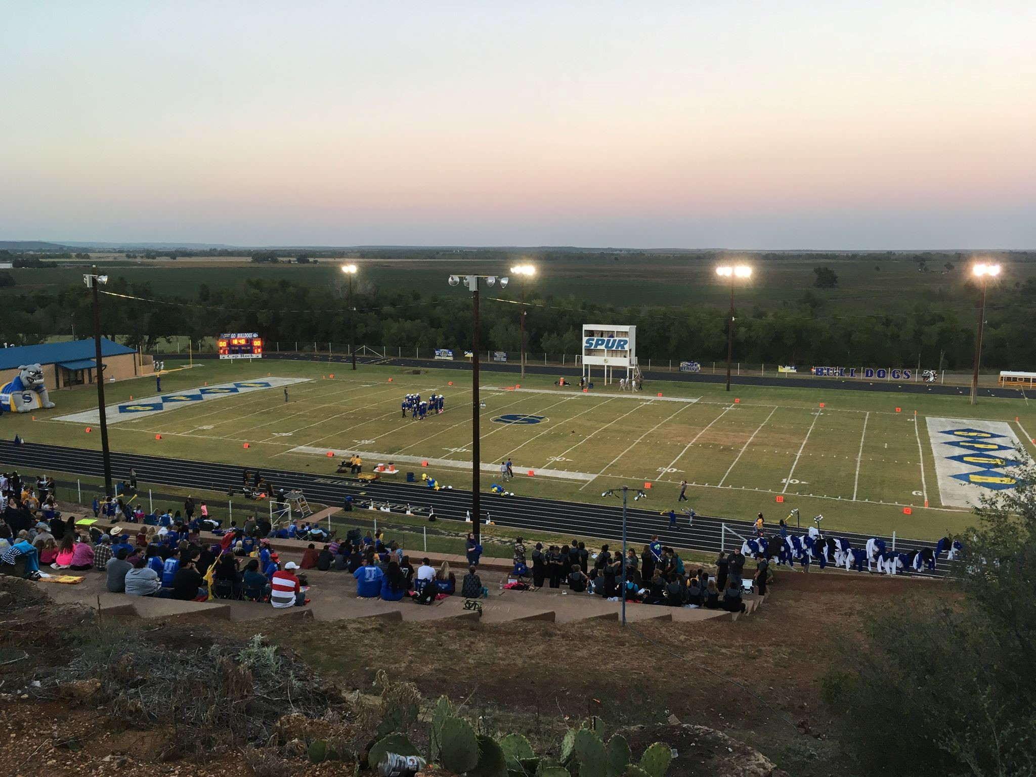 A photo of the football field, a few people gathered around it.