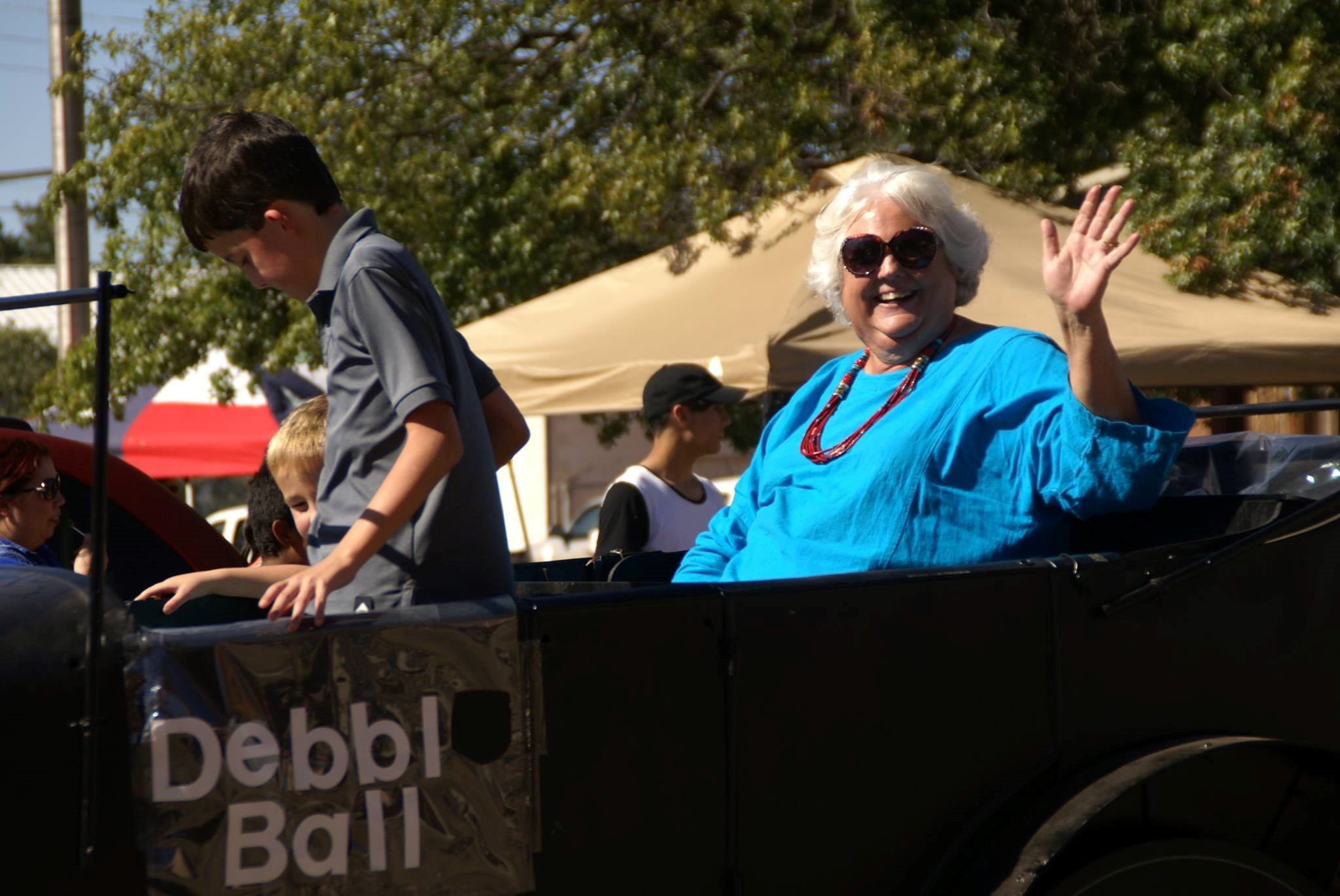 A photo of Debbie Ball, waving and cheering from her car.