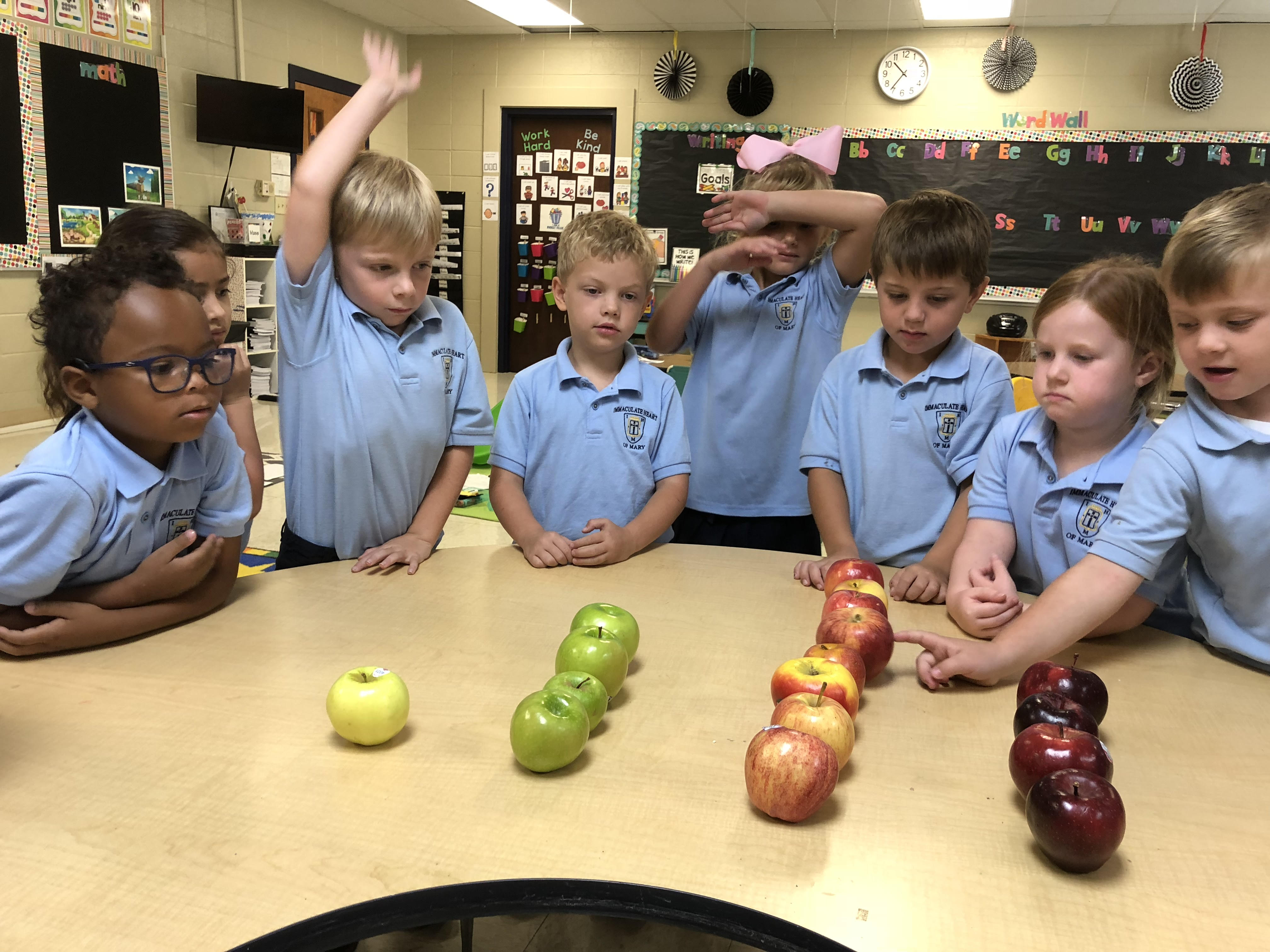 A group of students counting with apples