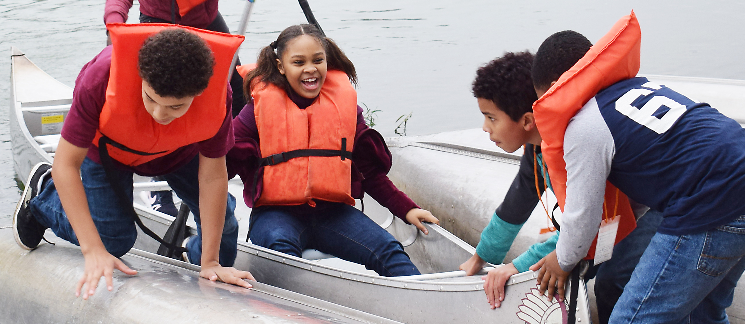 Students wearing life jackets laugh as they push a canoe into water