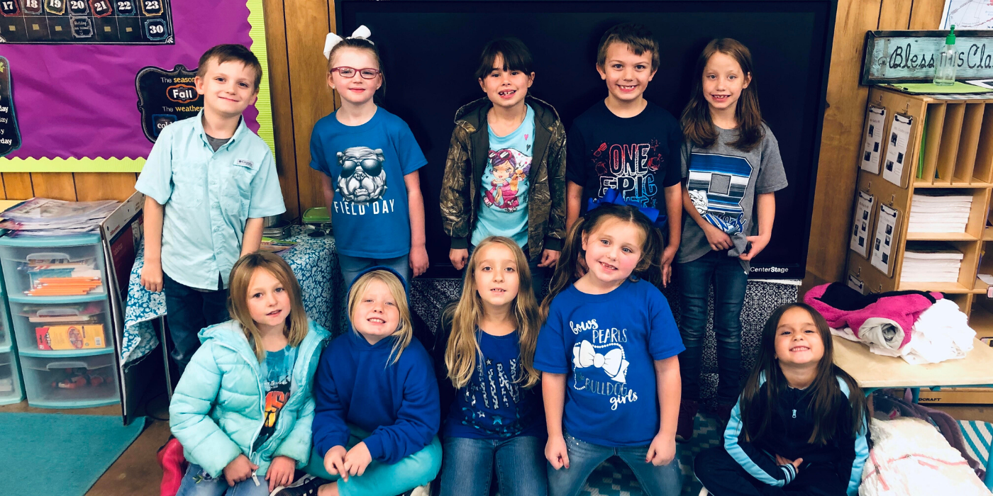 A group of elementary kids smiling at the camera all dressed up in different shades of blue.