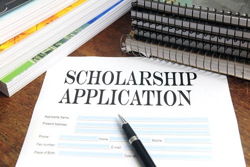 """A paper with the words """"Scholarship Application"""" is by the center of a table along with a couple of notebooks and textbooks."""