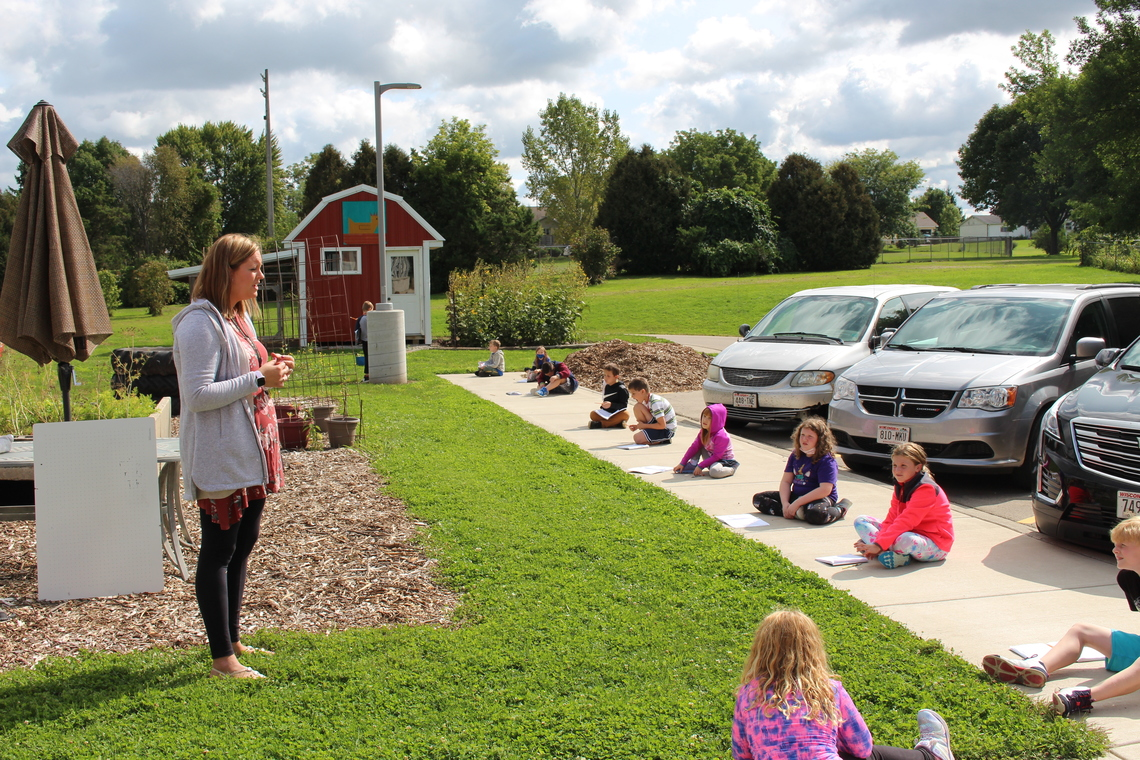 Teacher standing in grass and teaching students sitting spaced out on sidewalk