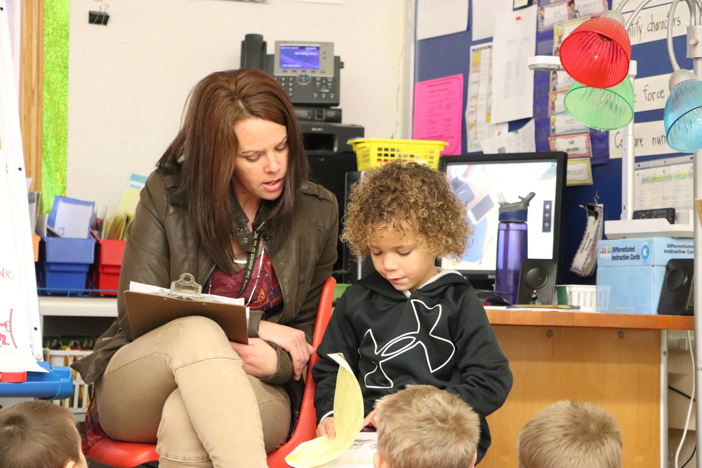 Photo of a person teaching a kid.