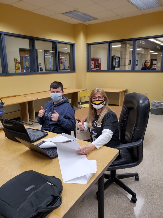 Student and teacher sitting at desk, wearing masks and giving thumbs up