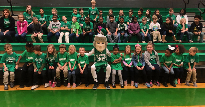 A photo of the School Mascot and some students in the gym.