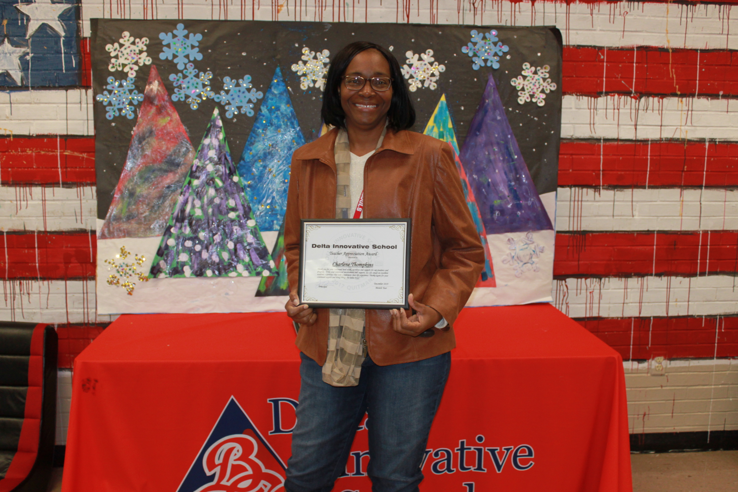 Photo of Teacher Thompkins with her Teacher of Quarter diploma.