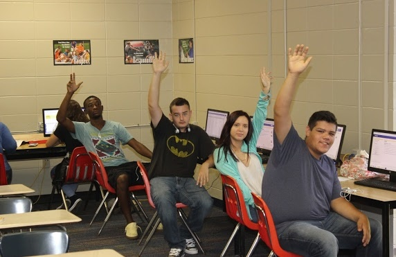 Photo of some students raising their hands in class.