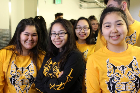 A photo of students wearing a T-shirt with the schools logo.