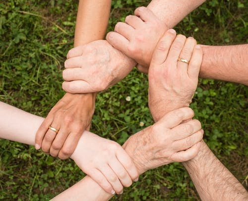 A photo with several hands holding each other forming a circle.