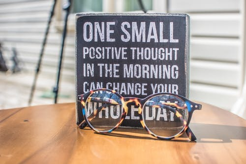 "A photo of a pair of glasses in a table with the phrase ""One small positive thought in the morning can change your whole day"" in the back."