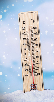 An image of a thermostat surrounded with snow.