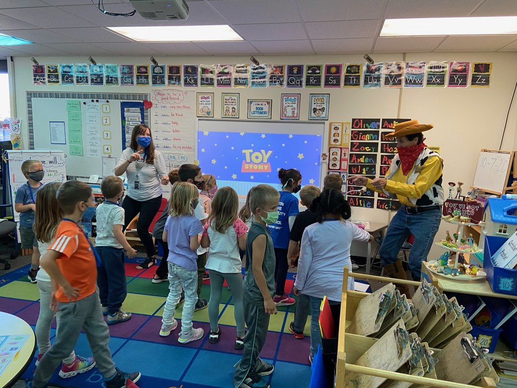 teacher and student with masks dancing in classroom with another teacher dressed as the character Woody from Toy Story