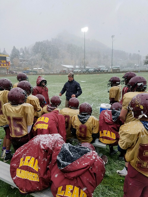 A photo of the football team paying attention to their coach while snowing.