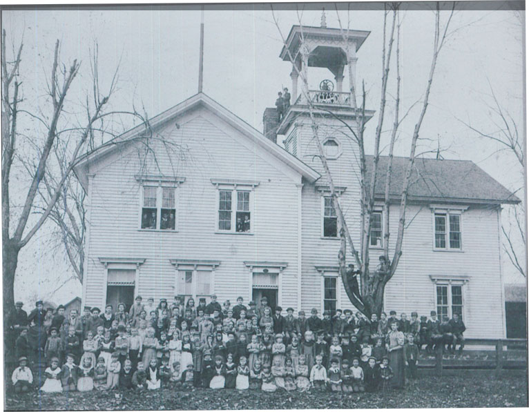 A black and white photo of all the students standing in front of the school's building.