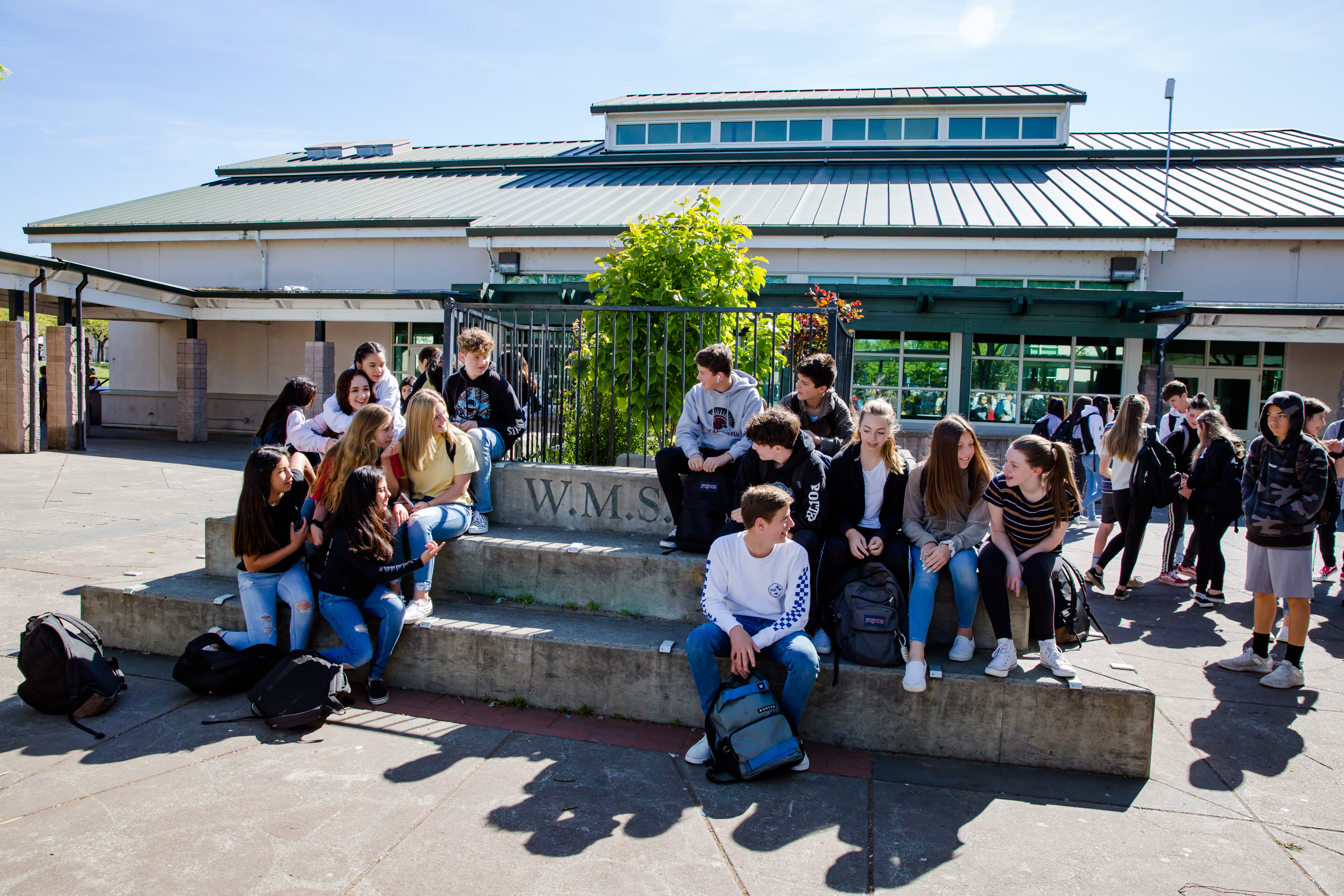 Windsor Middle Students sitting and chatting on the quad during break