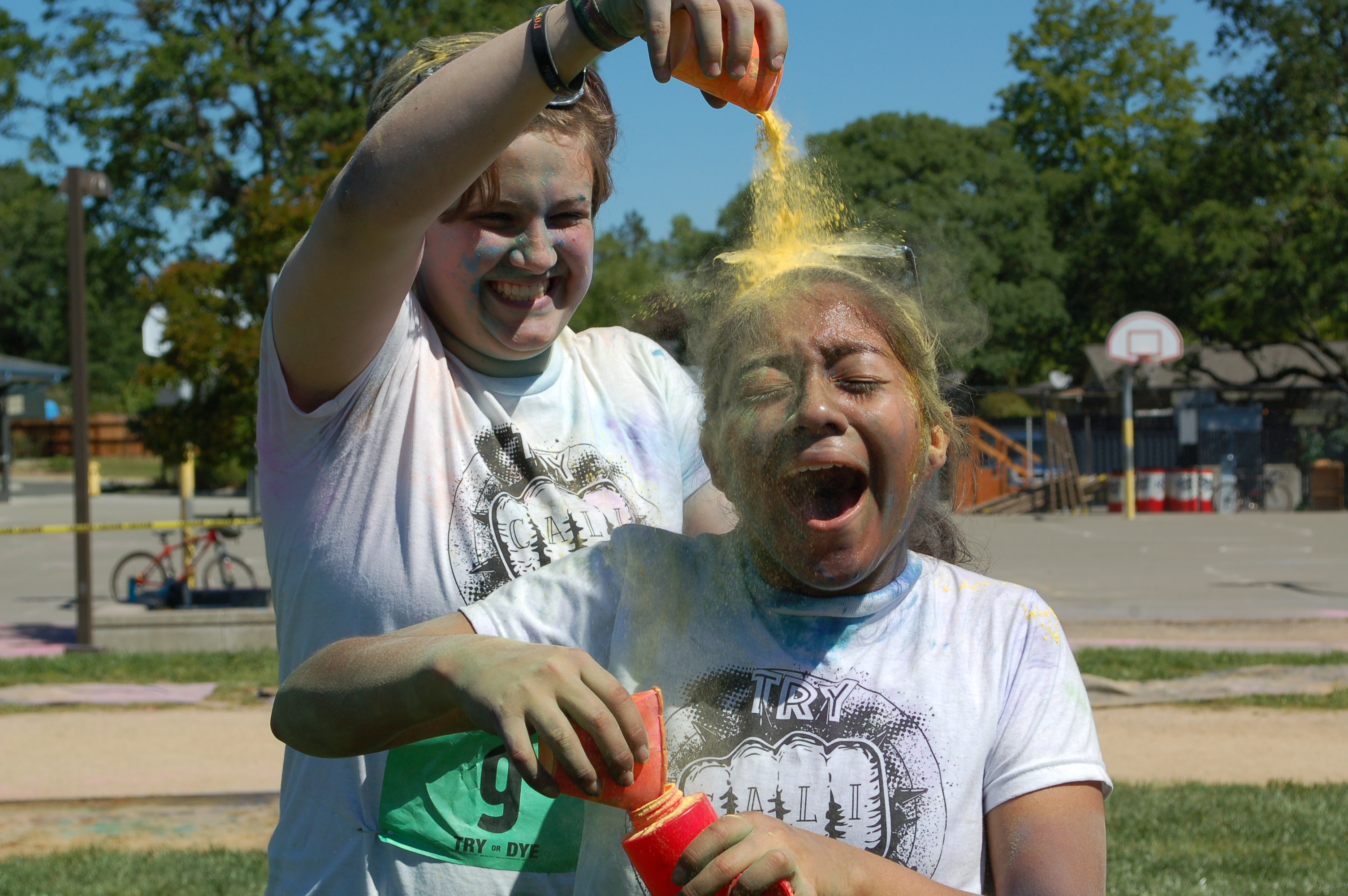 A photo of a student and a staff member playing with color powders.