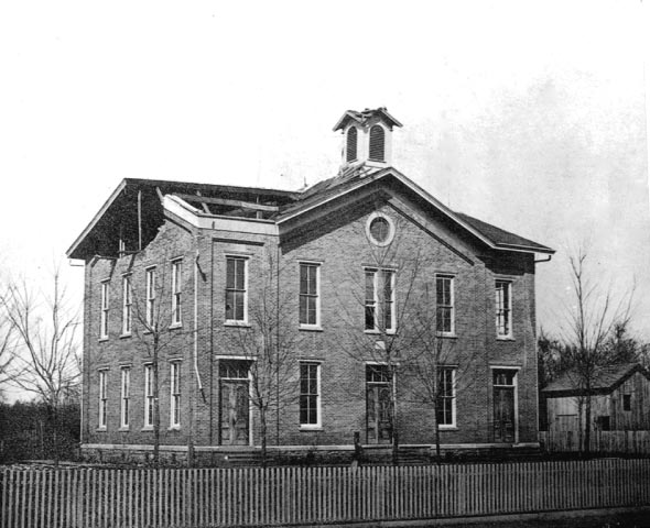 A black and white photo of the original school's building.