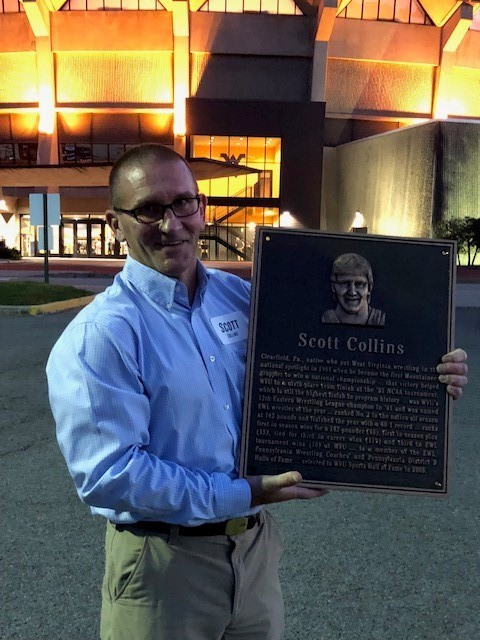 photo of scott collins holding up a plaque of himself