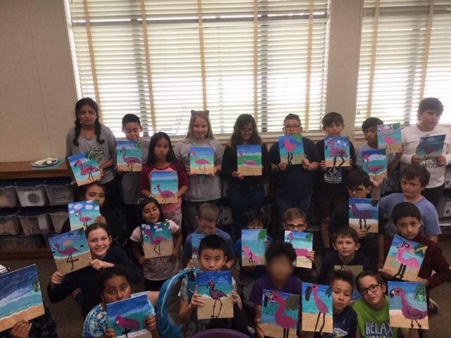 Photo of the students showing off their paintings