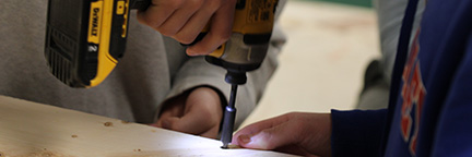 Students using a drill in shop class.