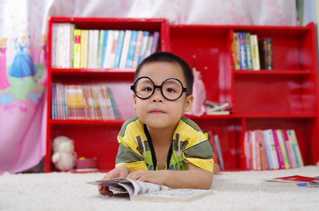 A photo of a kid reading a book.