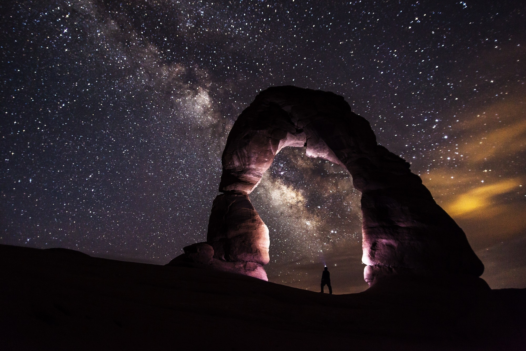 A photo of an arch with a sky full with stars at the background.