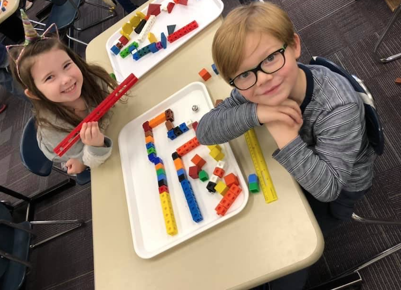Two kids playing with different legos and cubes to make a form
