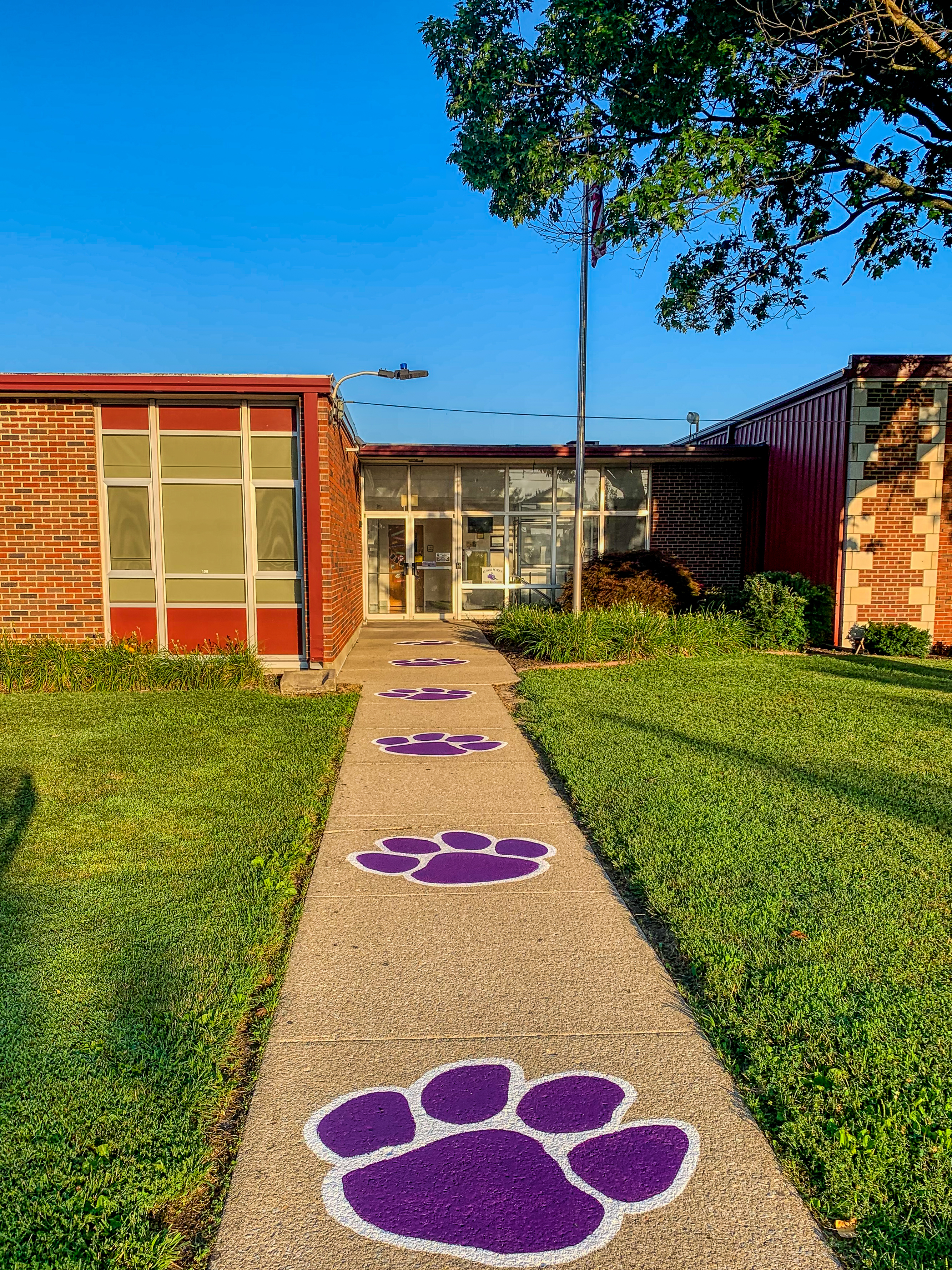 Image of front walk to Russell school with panther paws.