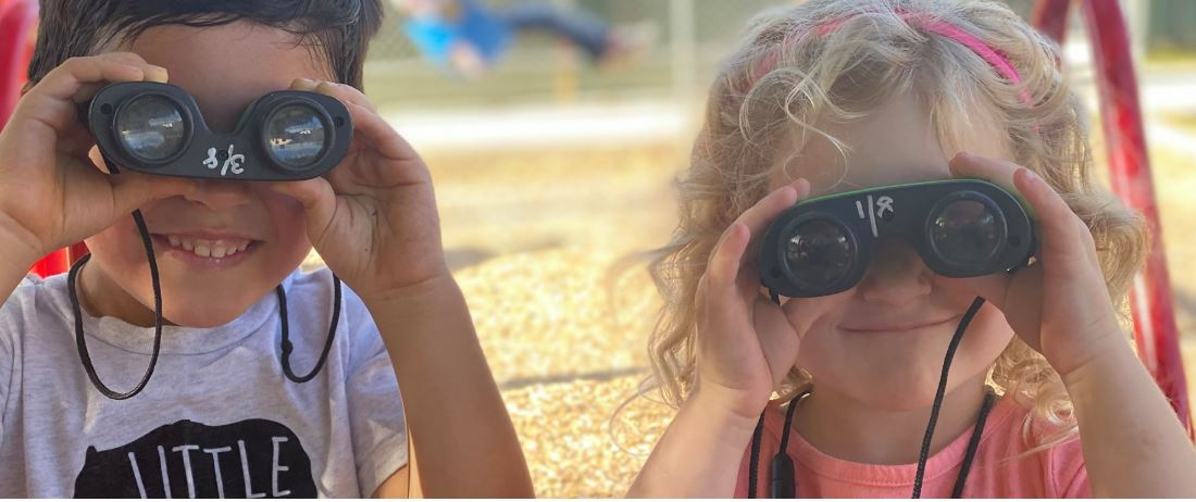 Two kids looking through a pair of binoculars