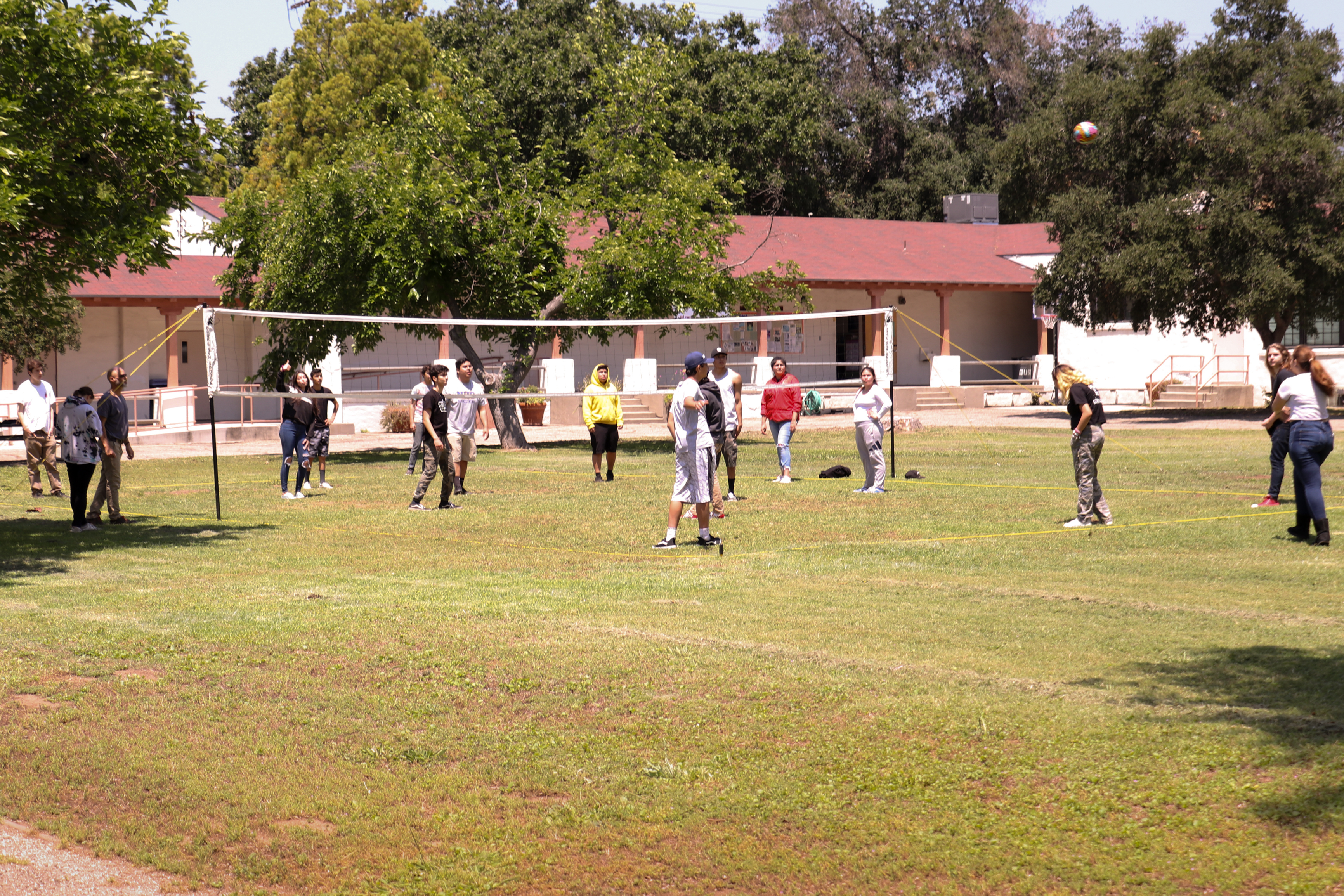 A group of teens all playing soccer in the school's field