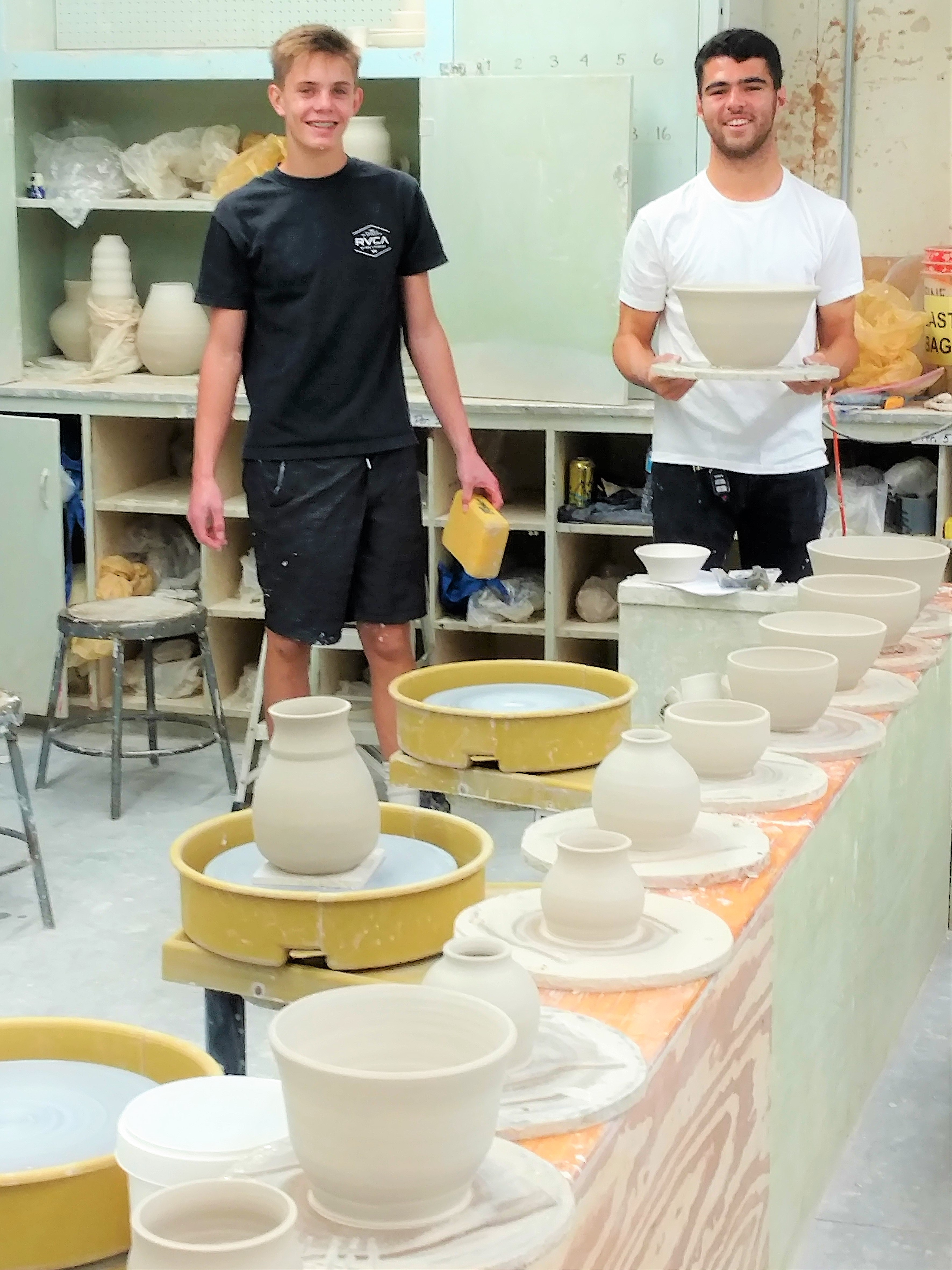 Two students smiling at the camera inside the ceramics classroom along with a row of ceramic plates and cups next to them.