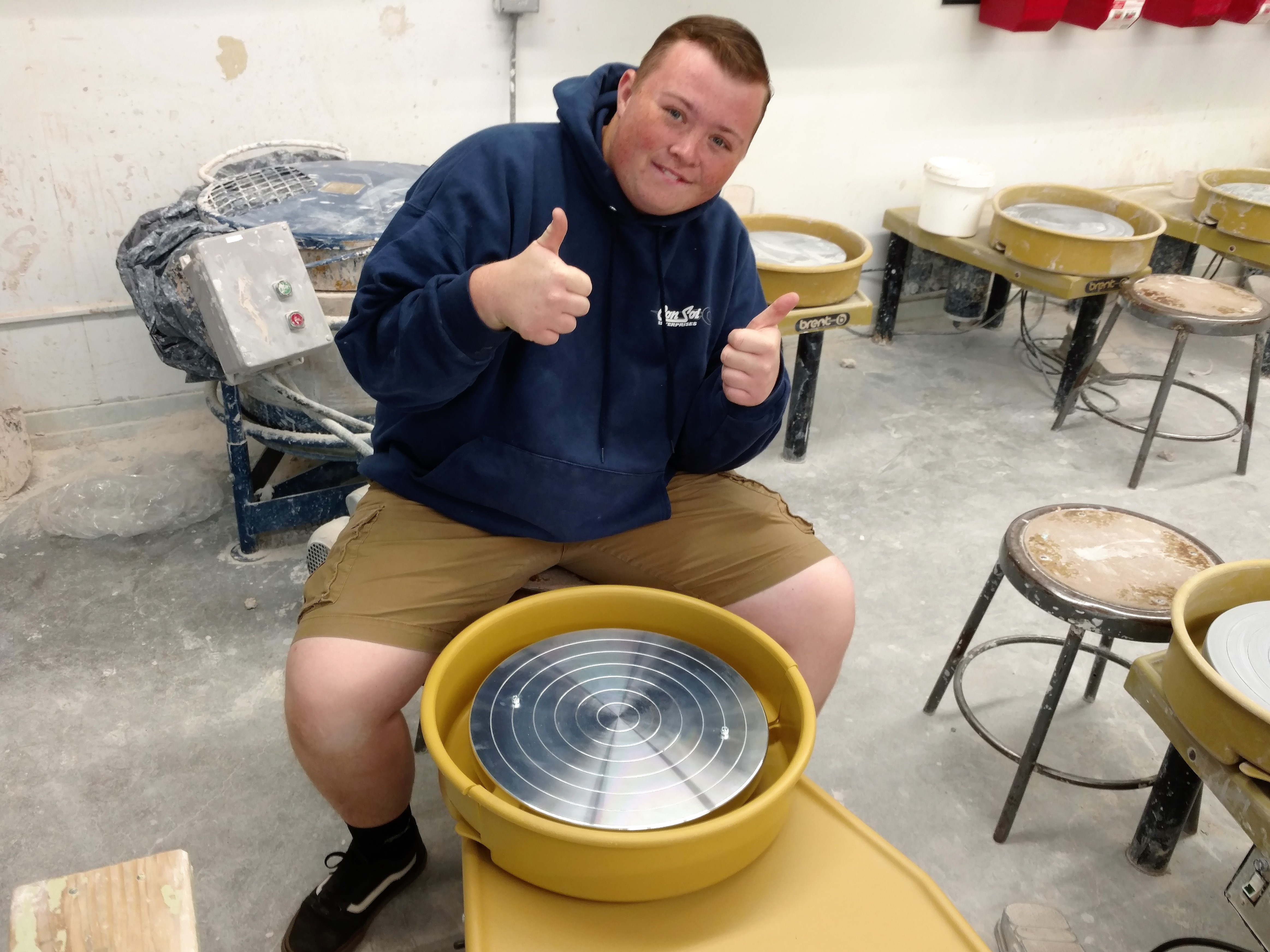 A high school student sitting in front of one of the pottery tools and showing his thumbs up