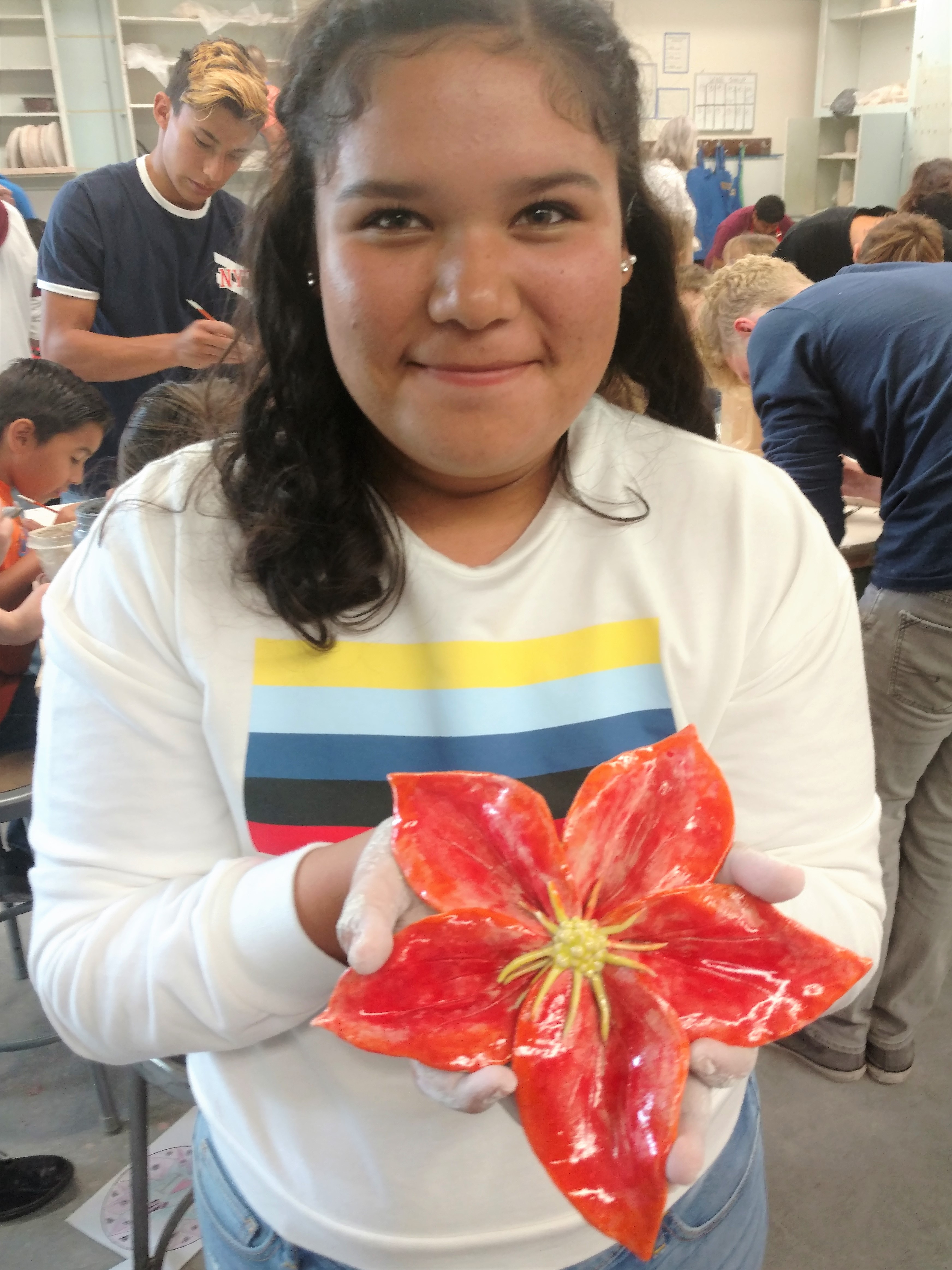 A girl holding up a ceramic flower
