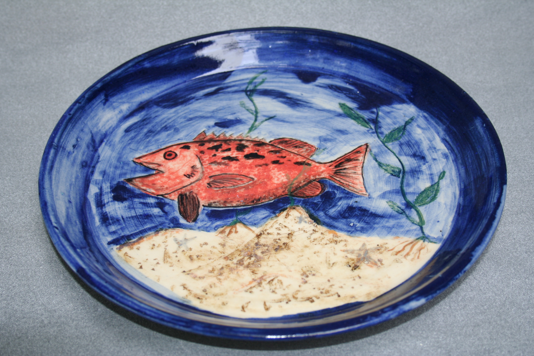 A ceramic plate along with a freshly painted fish over the base