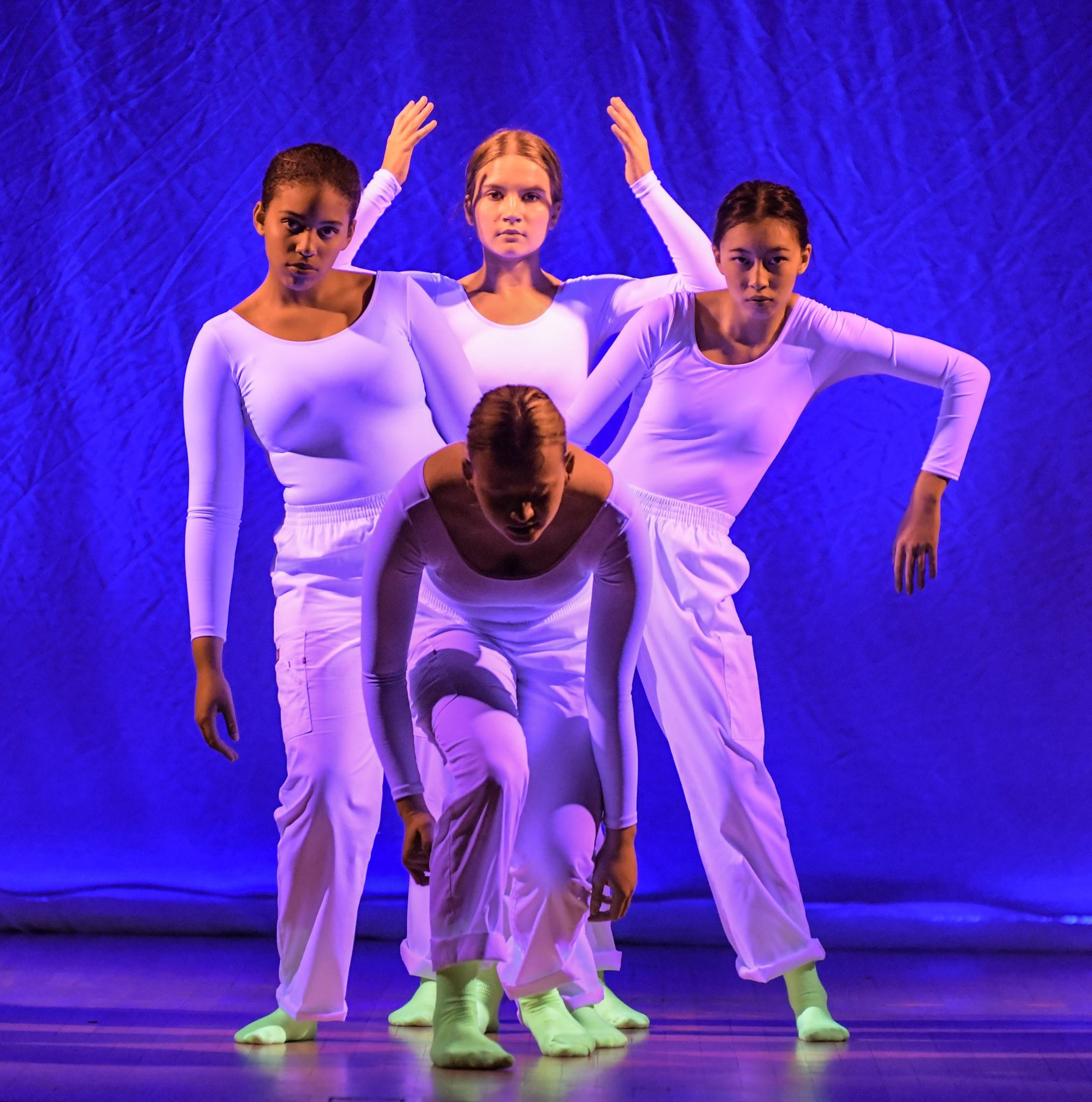 Four girls performing, all clad in white and bright green socks