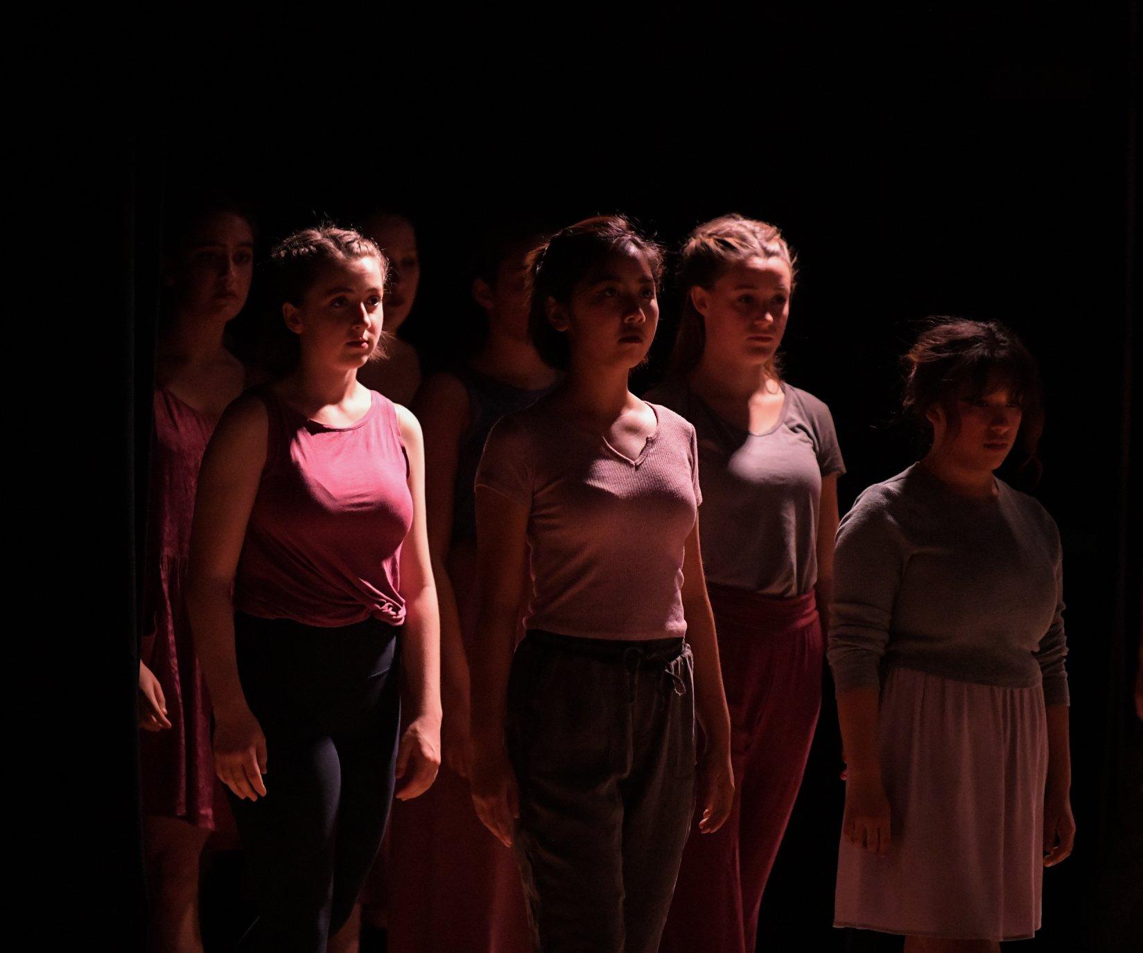 Seven girls standing still, the lighting shinning above their heads