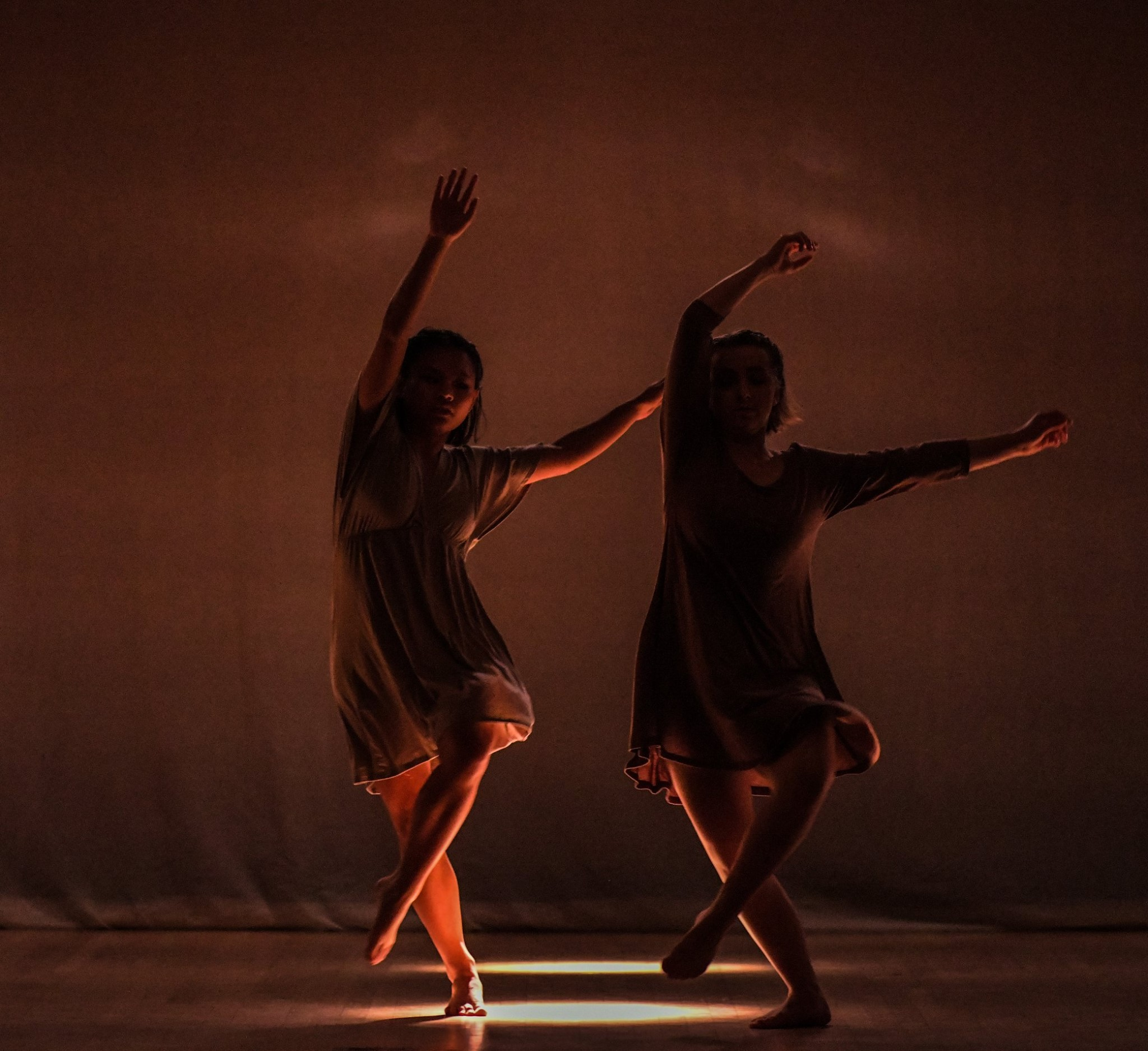 Two girls dancing and the lighting only illuminating the floor and their legs