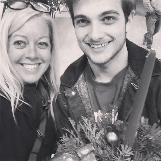 A black and white photo of a mother and her son, the boy holding onto a Christmas crown