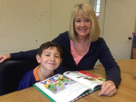 A photo of a teacher and a kid reading together a book