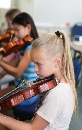 A row of students practicing the violin