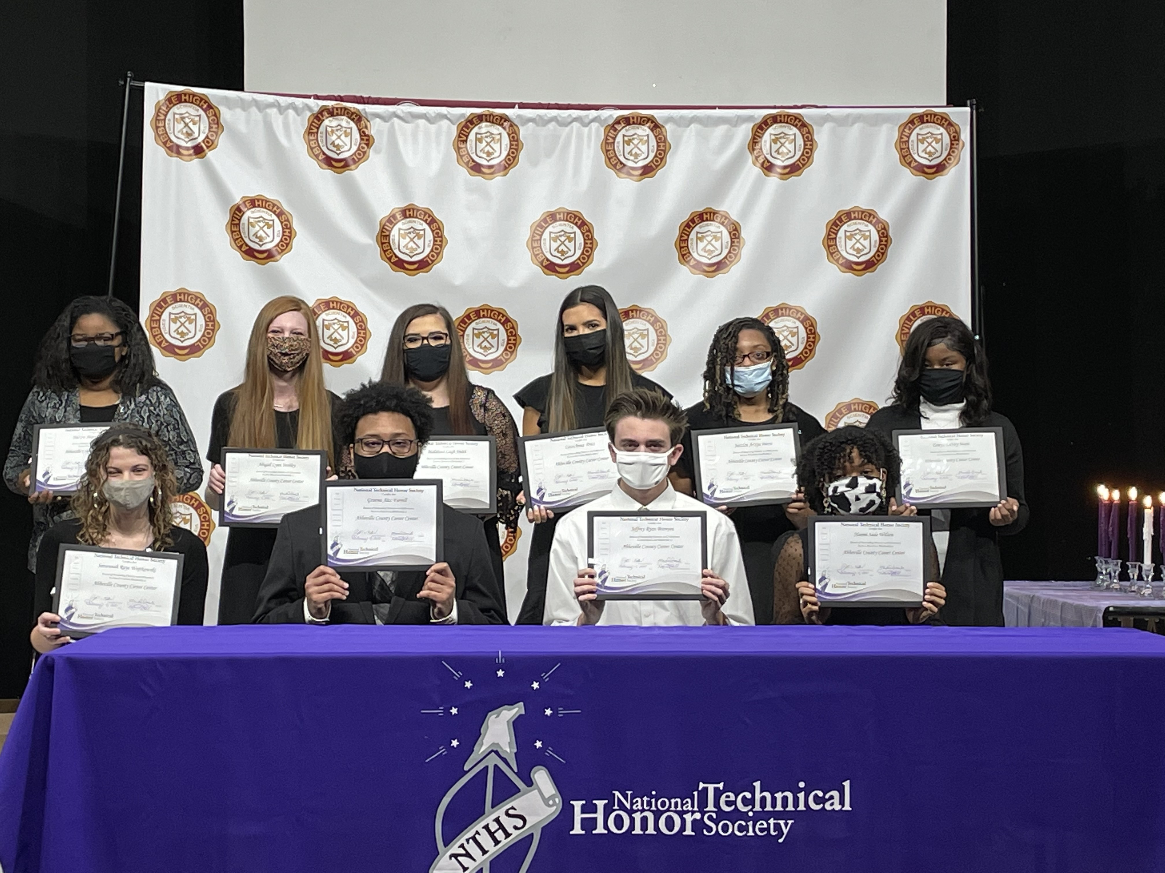 Students pose for camera wearing masks and holding plaques.