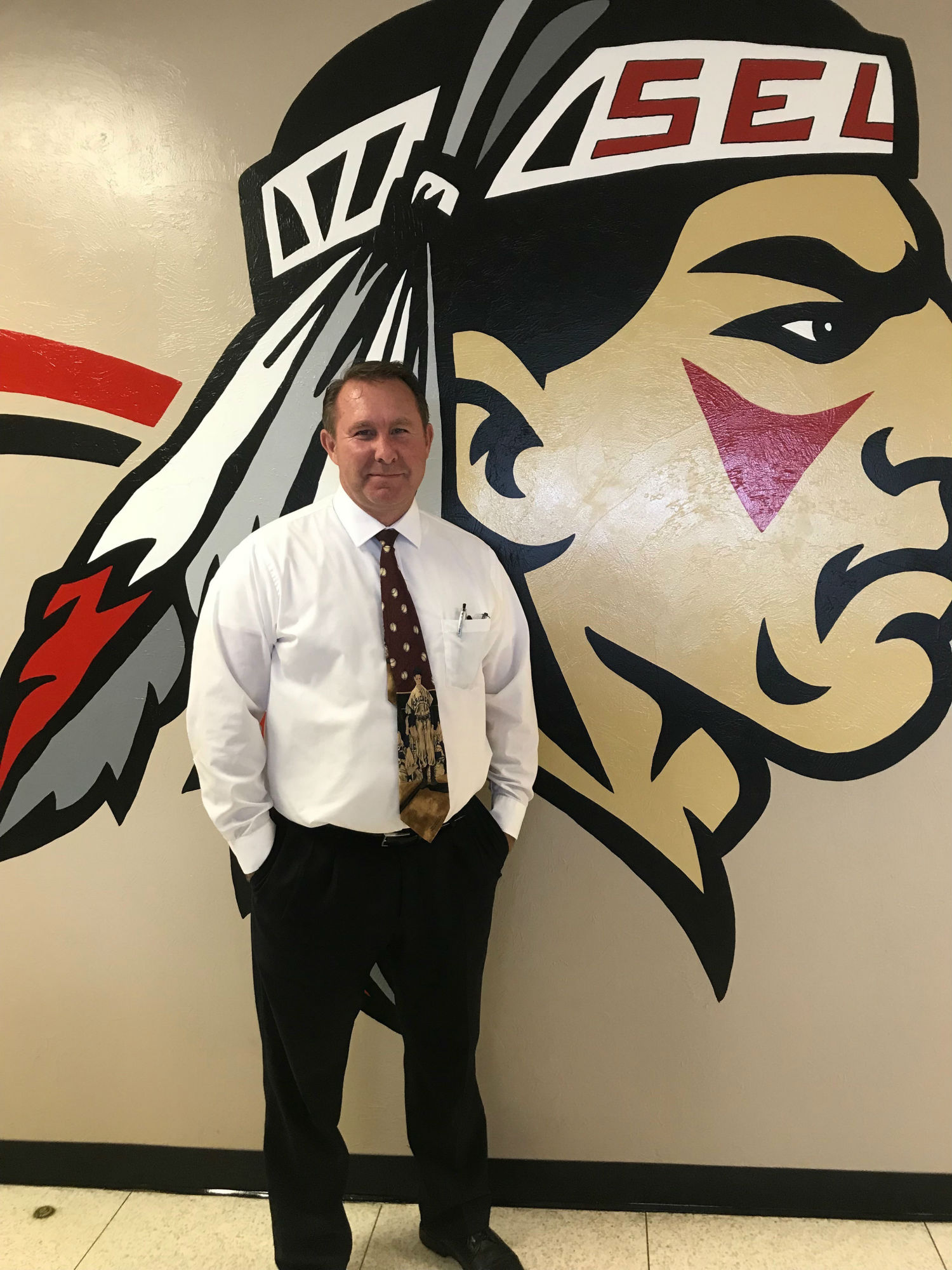 A photo of Principal Dennis Thompson in front of a school mascot mural