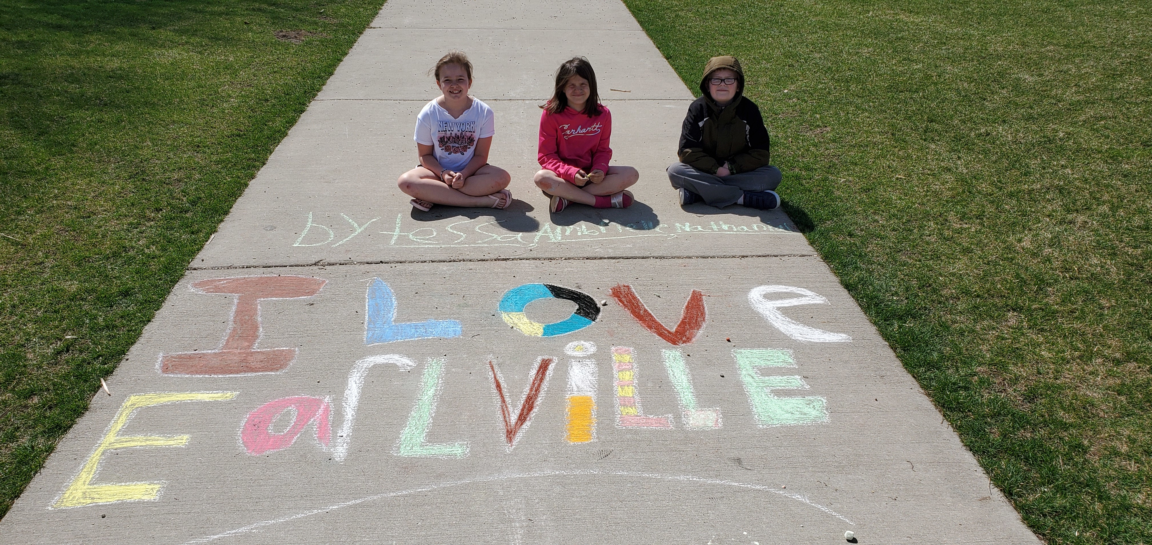 Students pose with a chalk drawing.