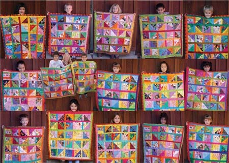 photo of students holding up quilts