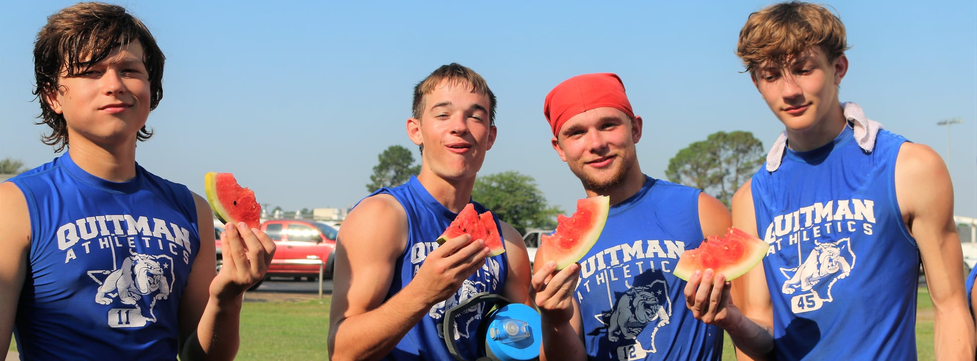 Football players eating watermelon after workout